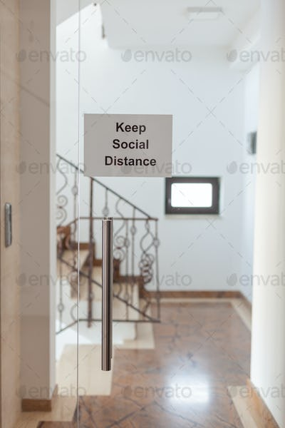 Glass office dor with keep social distance poster on it