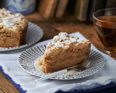Piece of Apple streusel Crumble Cake pie with crumbles and tea.