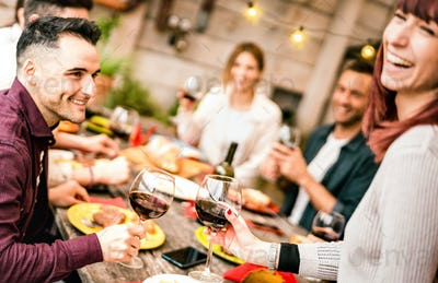 Happy couple toasting red wine with friends at rooftop party