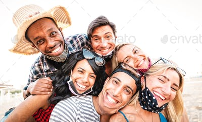 Multiracial friends taking selfie smiling over open face masks