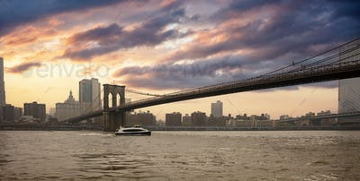 Brooklyn Bridge and Manhattan New York USA against cloudy sky at sunset