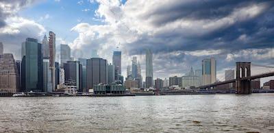 Brooklyn Bridge and Manhattan New York USA against blue cloudy sky