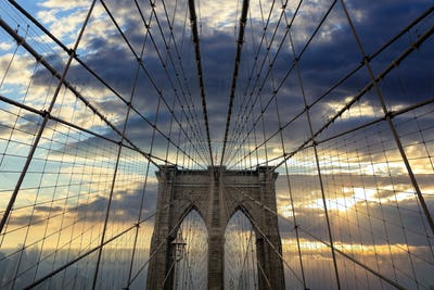 Brooklyn Bridge against cloudy sky at sunset. New York city, Manhattan. US