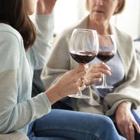 Close up of two women drinking wine at home