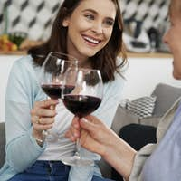 Two happy women toasting in wine at home