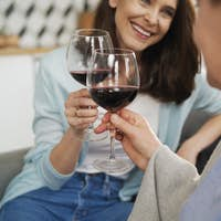 Close up of mother and adult daughter toasting in wine