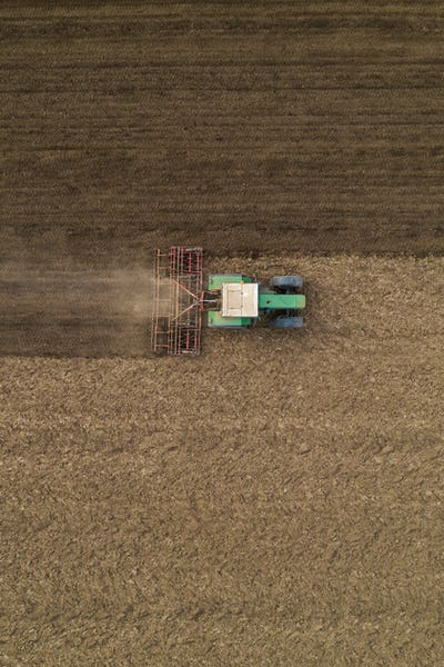 Aerial view of agricultural tractor tilling and harrowing ploughed field, directly above drone pov