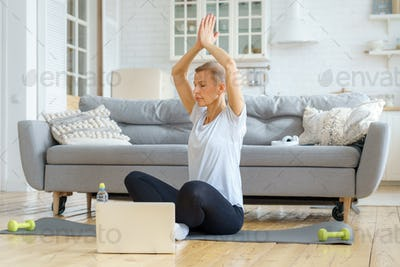 Senior woman spending time at home, online Training in living room. Exercising with Laptop