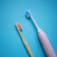 two ultrasonic electric toothbrushes on a blue background