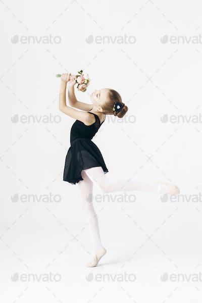 Delicate girl ballerina dancing on white background