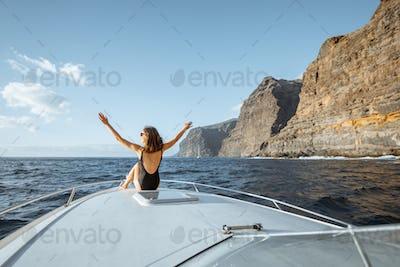 Woman sailing on the yacht near the rocky coast