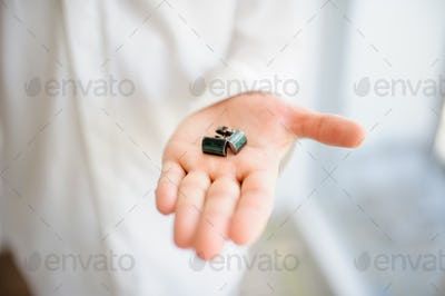 A man shows cufflinks on his hand. Close-up.