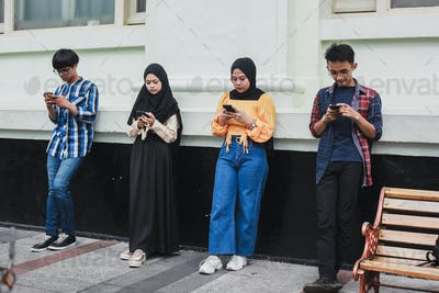 Group of people standing with distance and using smartphone together