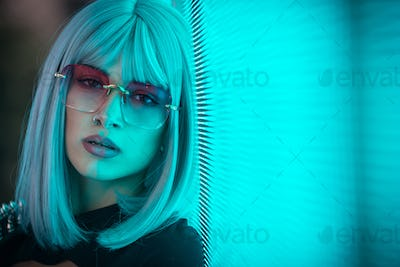 Image of a beautiful young woman posing against a led panel.