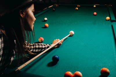 A girl in a hat in a billiard club with a cue in her hands hits a ball.Playing billiards