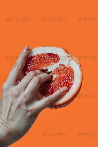 Image of a female hand with fingers inside a fresh grapefruit