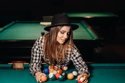 A girl in a hat in a billiard club with balls in her hands.Playing pool