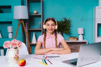 Cinematic image of a young little girl sitting at home and using the computer