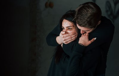 Man's hand covering her mouth. Kidnapped woman is threatened by guy