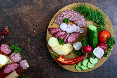 Sliced sausage and fresh vegetables on a wooden tray. Snack tray. Top view.