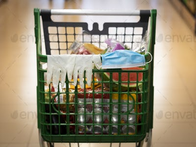 Coronavirus.Close-up of a shopping cart with protective gloves and mask resting on the handlebar