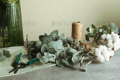 Floristic concept with eucalyptus, flowers and cotton on gray table