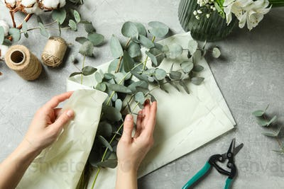 Woman wraps eucalyptus in paper on gray textured table