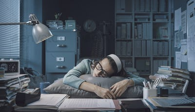 Exhausted office worker sleeping at her desk