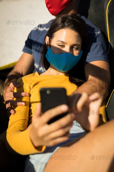Happy caucasian couple wearing face masks sitting in beach buggy taking selfies