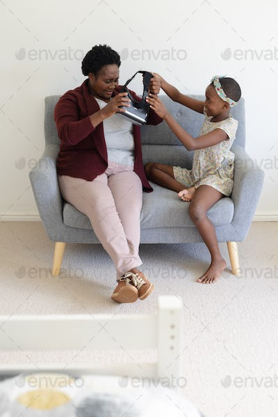 African american grandmother sitting on couch putting on vr headset with help from granddaughter
