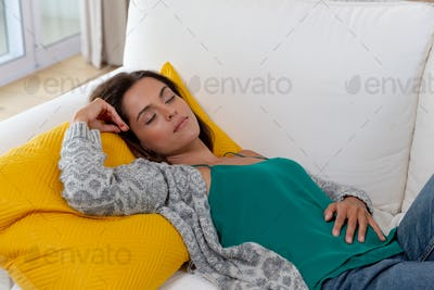 Caucasian woman lying on a couch and sleeping
