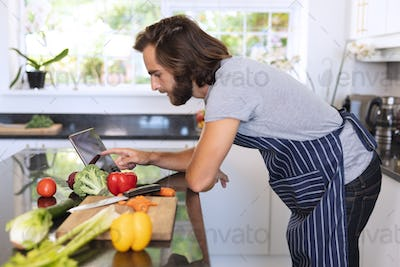 Caucasian man in kitchen wearing apron and using tablet