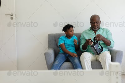 Senior african american grandfather holding vr headset sitting on couch beside grandson