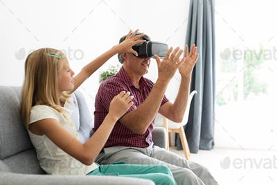 Caucasian granddaughter sitting on couch beside grandfather adjusting his vr headset