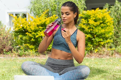 Caucasian woman drinking water after exercising and using laptop in garden