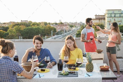 Happy young people eating and drinking wine together at barbecue party