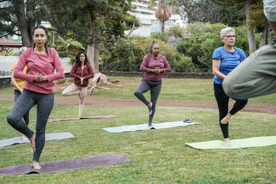 Multiracial people doing yoga class outdoor in city park - Focus on african woman face