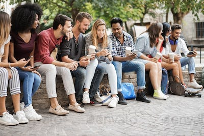 Group of friends using mobile phones outdoors in city park - Main focus on african girl face