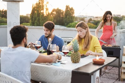 Young friends having barbecue party outdoors