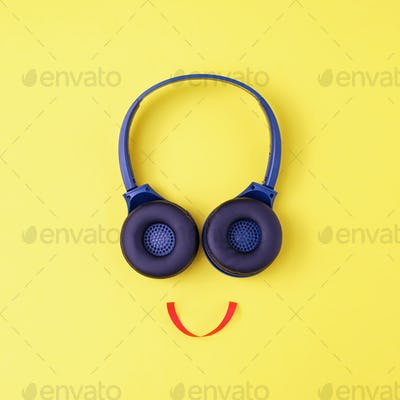 Headphones on a yellow background in the form of a happy face with a smile