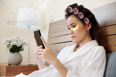 Woman resting in bed with smartphone