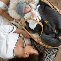 Little boy in a wicker cradle with a toy on the background of a blanket.