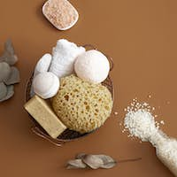 Spa composition with bath accessories on brown background.