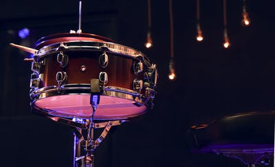 Snare drum and drumsticks close up in dark.