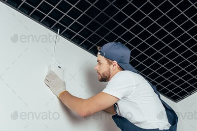 low angle view of young electrician fixing home alarm on wall