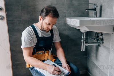 adult male plumber with toolbelt writing in clipboard near broken sink in bathroom