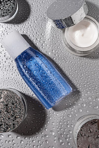 top view of micellar water and body creams with water drops on grey background