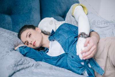 pensive woman lying on bed with mannequin behind, one way love concept