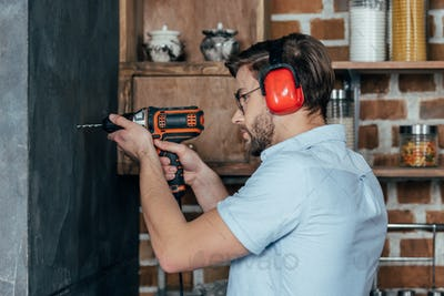 side view of young man in eyeglasses and earmuffs drilling wall with electric drill