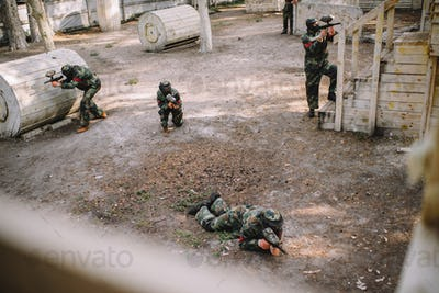 high angle view of paintball team in uniform and protective masks playing paintball with markers